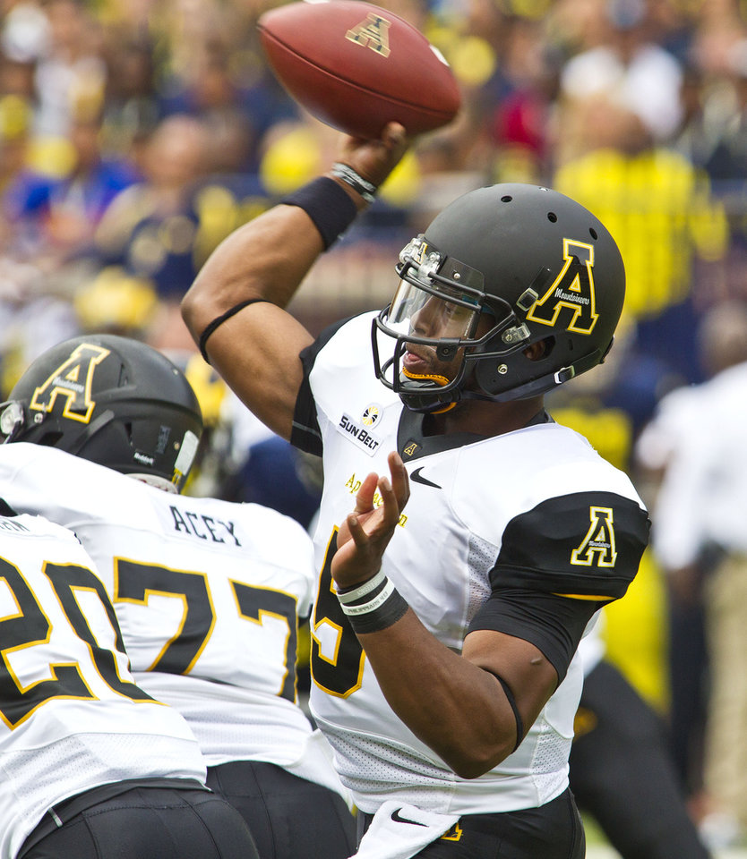 Photo - Appalachian State quarterback Kameron Bryant (5) throws a pass in the first quarter of  an NCAA college football game against Michigan in Ann Arbor, Mich., Saturday, Aug. 30, 2014. (AP Photo/Tony Ding)