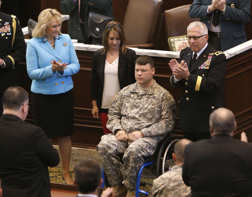 Photo -  Oklahoma Gov. Mary Fallin and Maj. Gen. Myles Deering present a medal and commendation to Sgt. E.H. Pittman during a joint session of the Oklahoma Legislature on Tuesday in Oklahoma City. Pittman, also shown with his wife, Jean, suffered major injuries while protecting others during the May 20 tornado in Moore. Photo by Paul Hellstern, The Oklahoman   PAUL HELLSTERN -