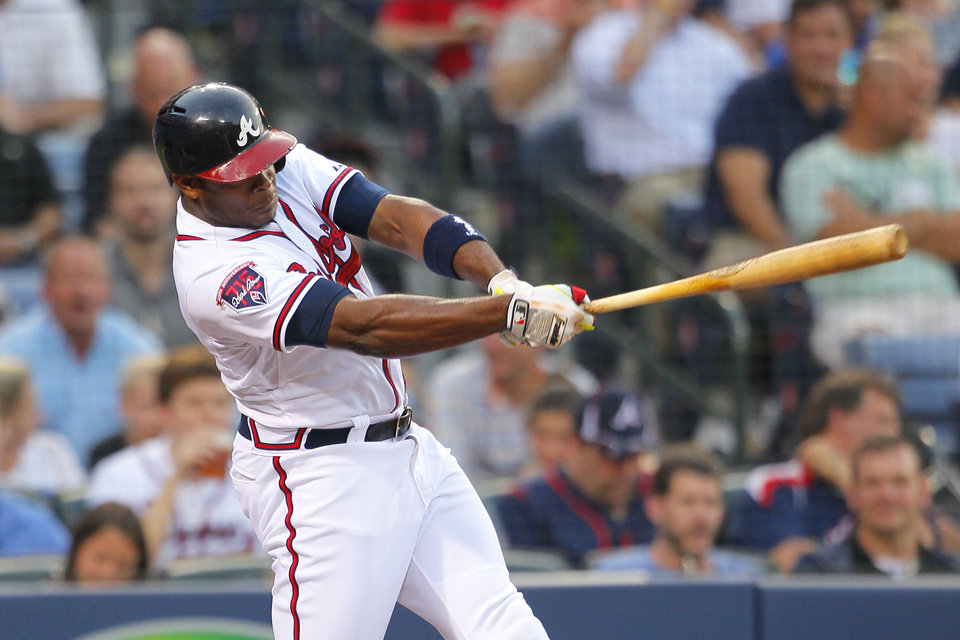 Photo - Atlanta Braves' Justin Upton swings on a two-run double in the third inning of a baseball game against the Milwaukee Brewers on Tuesday, May 20, 2014, in Atlanta. (AP Photo/Todd Kirkland)