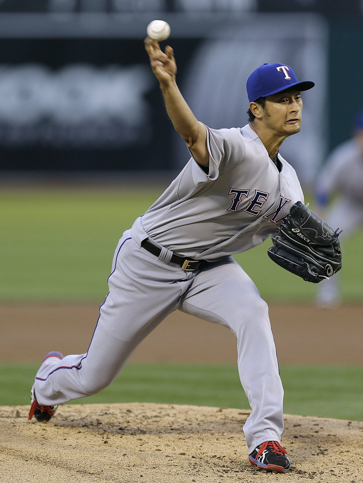 Photo - Texas Rangers' Yu Darvish works against the Oakland Athletics in the first inning of a baseball game Monday, April 21, 2014, in Oakland, Calif. (AP Photo/Ben Margot)