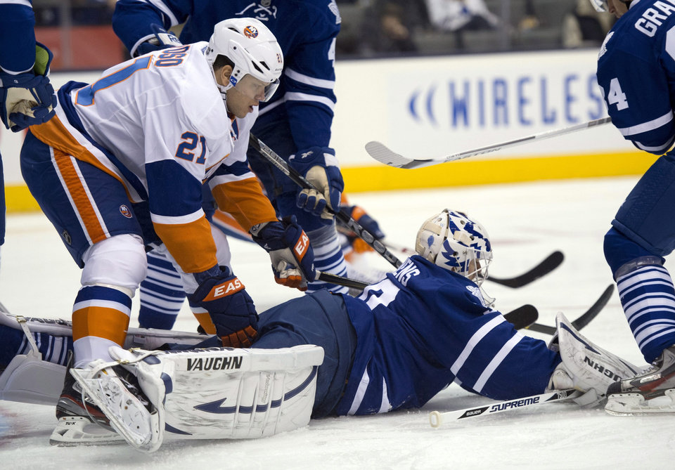 Toronto Maple Leafs goaltender Ben Scrivens battles for the puck with New York Islanders right winger Kyle Okposo (21) during the first period of an NHL hockey game in Toronto on Thursday, Jan. 24, 2013. (AP Photo/The Canadian Press, Frank Gunn)