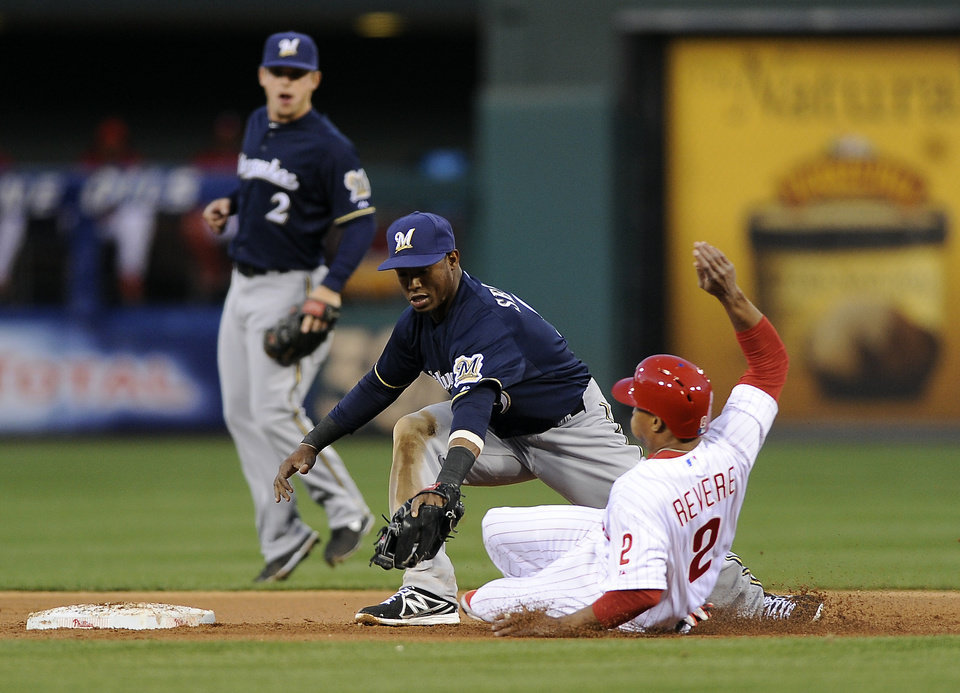 Photo - Philadelphia Phillies' Ben Revere, right, slides into second base and tries to beat a tag from Milwaukee Brewers shortstop Jean Segura during the first inning of a baseball game on Wednesday, April 9, 2014, in Philadelphia. (AP Photo/Michael Perez)