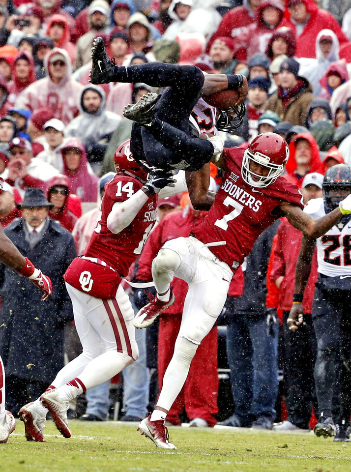 Photo - Oklahoma's Emmanuel Beal (14) and Jordan Thomas (7) combine to take down Oklahoma State's Chris Carson (32)  during the Bedlam college football game between the Oklahoma Sooners (OU) and the Oklahoma State Cowboys (OSU) at Gaylord Family - Oklahoma Memorial Stadium in Norman, Okla., Saturday, Dec. 3, 2016. Photo by Steve Sisney, The Oklahoman