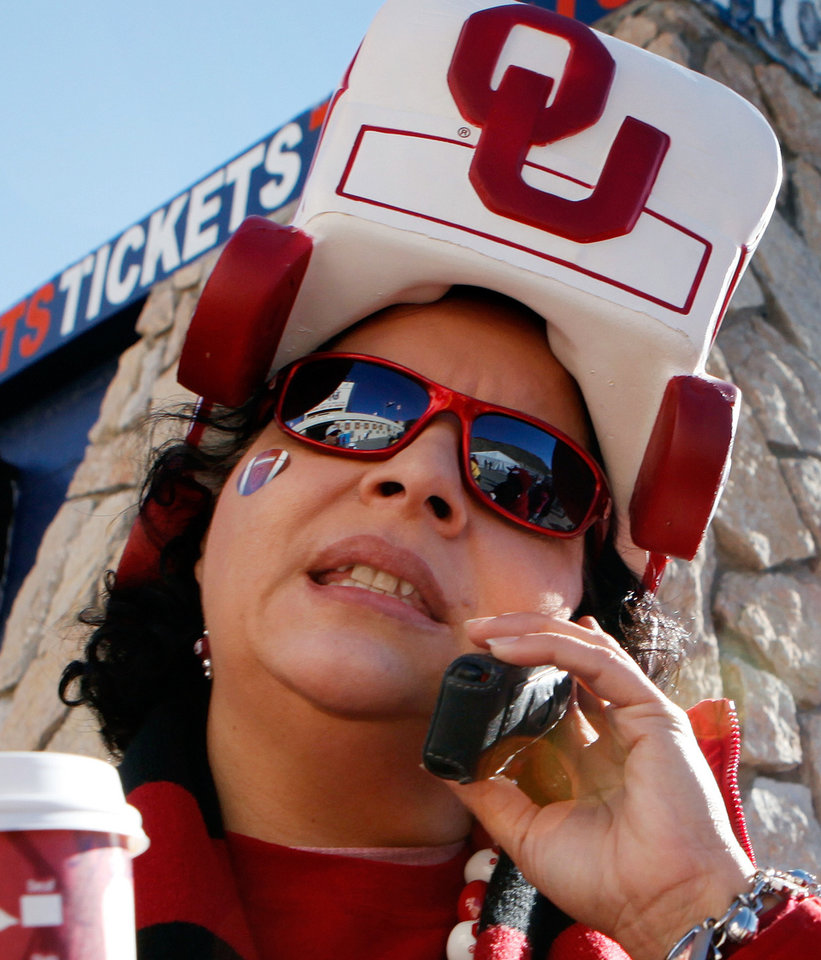 Photo - Jessica Santiago, El Paso, mother of OU band member Stephanie Santiago, talks on her phone near the ticket booth before the college football game between the University of Oklahoma Sooners (OU) and the Stanford University Cardinal on Thursday, Dec. 31, 2009, in El Paso, Tex.   Photo by Steve Sisney, The Oklahoman