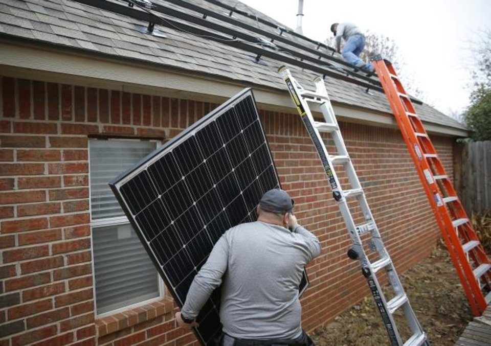 Photo -  Alex Lopez, with Solar Power of Oklahoma, carries a solar panel to the side of an area  home where an installation was underway in 2019. [BRYAN TERRY/THE OKLAHOMAN ARCHIVES]
