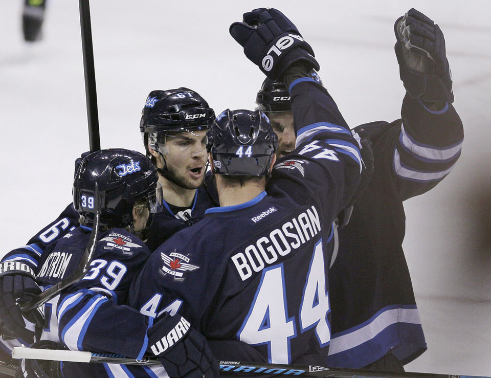 Photo - Winnipeg Jets' Tobias Enstrom (39), Michael Frolik (67), Zach Bogosian (44) and Andrew Ladd (16) celebrate Bogosian's goal against the Vancouver Canucks during the first period of an NHL hockey game in Winnipeg, Manitoba, on Friday, Jan. 31, 2014. (AP Photo/The Canadian Press, John Woods)