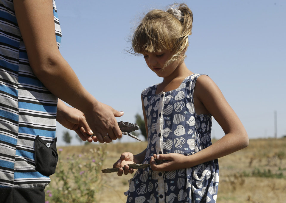 Photo - Ksenia Plyushch shows pieces of shrapnel to her mother in the village of Osykove, eastern Ukraine, Tuesday, Sept. 2, 2014. Pro-Russian rebels have been fighting Ukrainian government troops since mid-April in a conflict that has left more than 2,500 people dead and forced at least 340,000 to flee. In the last week, the rebels have scored significant gains on the ground, launching a new offensive along the Sea of Azov coast. (AP Photo/Sergei Grits)
