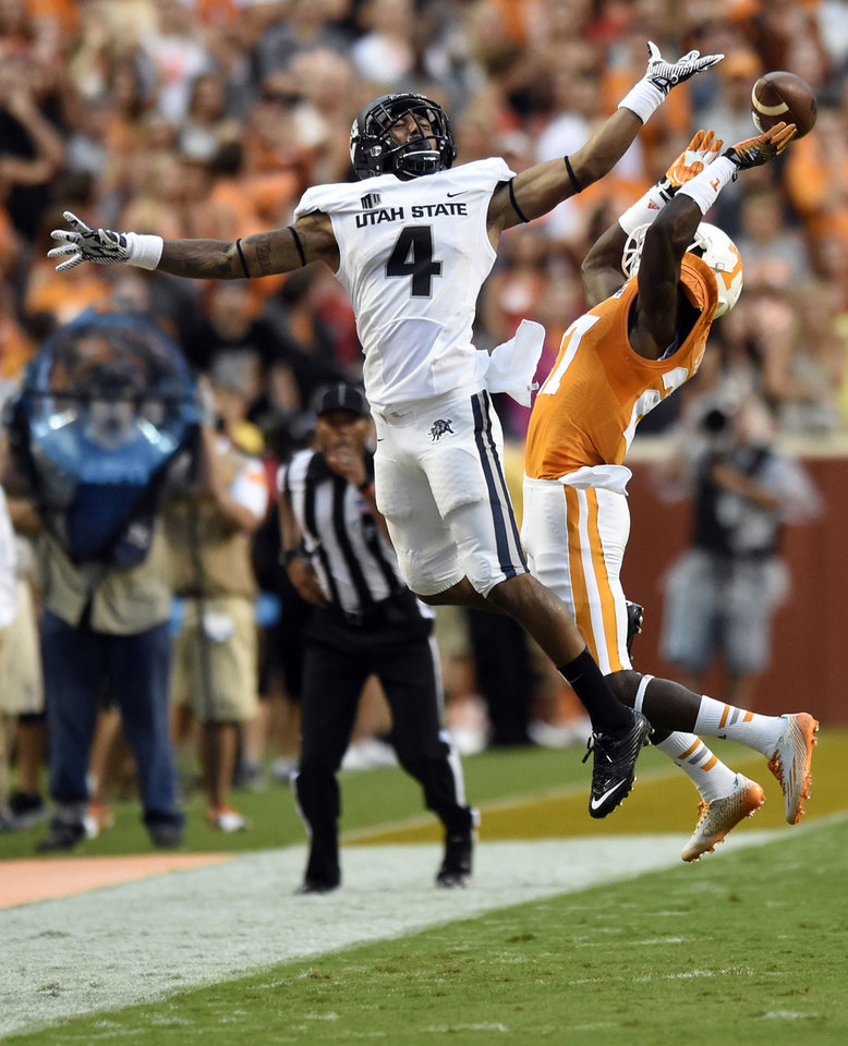 Photo - Tennessee defensive back Justin Coleman (27) breaks up a pass intended for Utah State wide receiver Hunter Sharp (4) during their NCAA college football game at Neyland Stadium, Sunday, Aug. 31, 2014 in Knoxville, Tenn. Coleman was called for pass interference during the play.   (AP Photo/Knoxville News Sentinel, Saul Young)