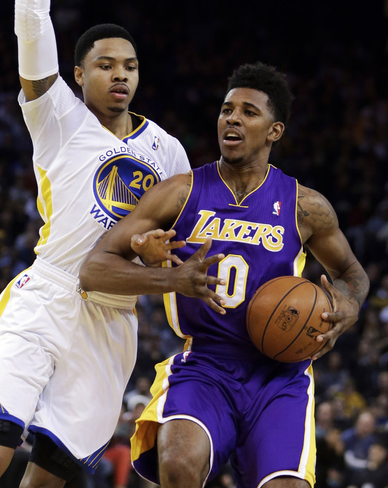 Photo - Golden State Warriors' Kent Bazemore, left, guards Los Angeles Lakers' Nick Young (0) during the first half of an NBA basketball game Saturday, Dec. 21, 2013, in Oakland, Calif. (AP Photo/Ben Margot)