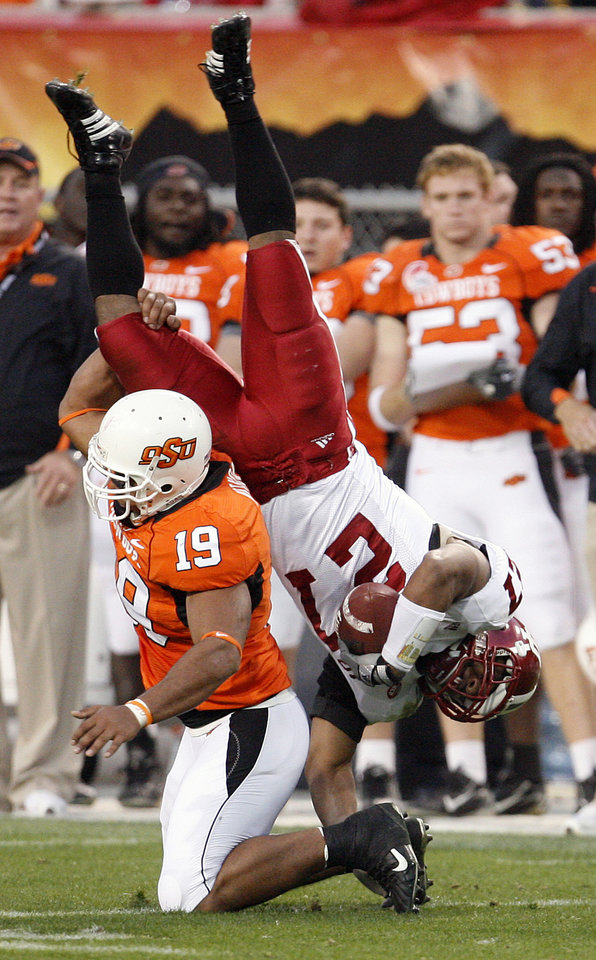 Photo - Oklahoma State's Jeremy Nethon (19) up ends Indiana's Bryan Payton (27) in the first half during the Insight Bowl college football game between Oklahoma State University (OSU) and the Indiana University Hoosiers (IU) at Sun Devil Stadium on Monday, Dec. 31, 2007, in Tempe, Ariz. 