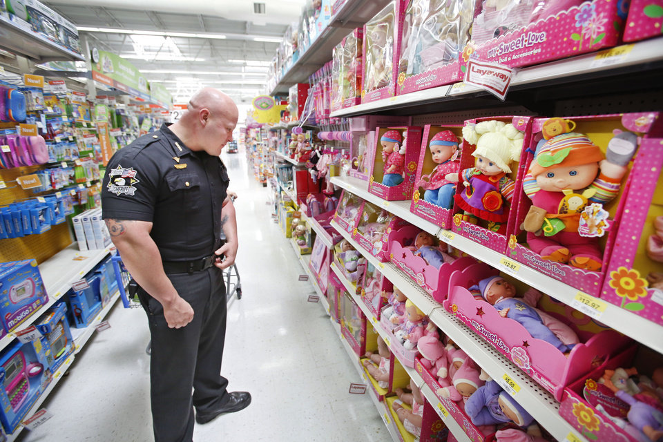 Oklahoma County sheriff's Deputy James Palmer shops for toys during a Sunbeam Family Services Christmas shopping event at a Walmart in Oklahoma City. The event helps furnish Christmas gifts for underprivileged children throughout the Oklahoma City metropolitan area. Photos By Steve Gooch, The Oklahoman