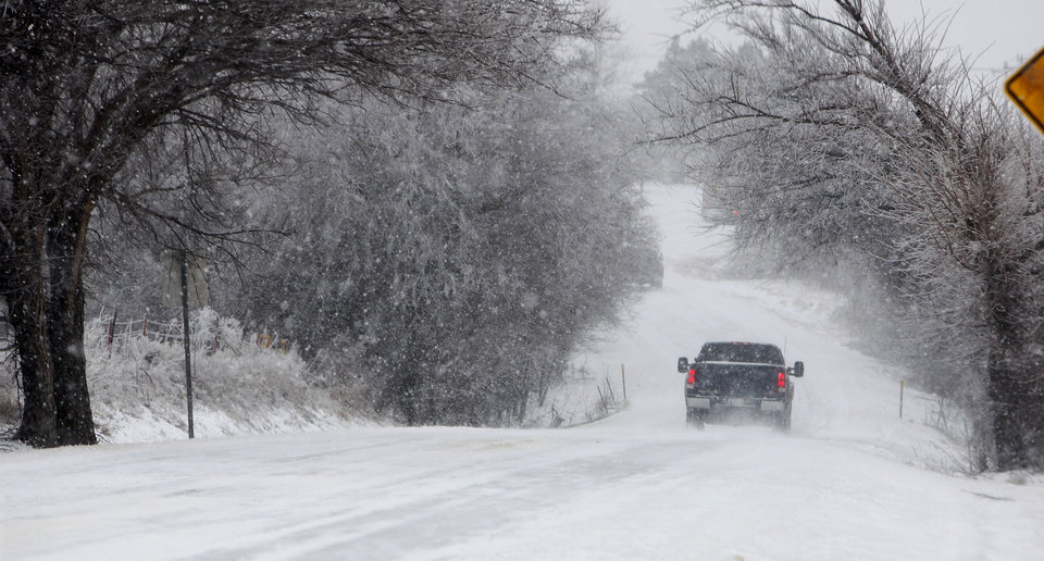 Photo - A vehicle travels down a hill in the falling snow on SH 4 between Piedmont and Yukon Friday, Jan. 29, 2010. Photo by Paul B. Southerland, The Oklahoman ORG XMIT: KOD