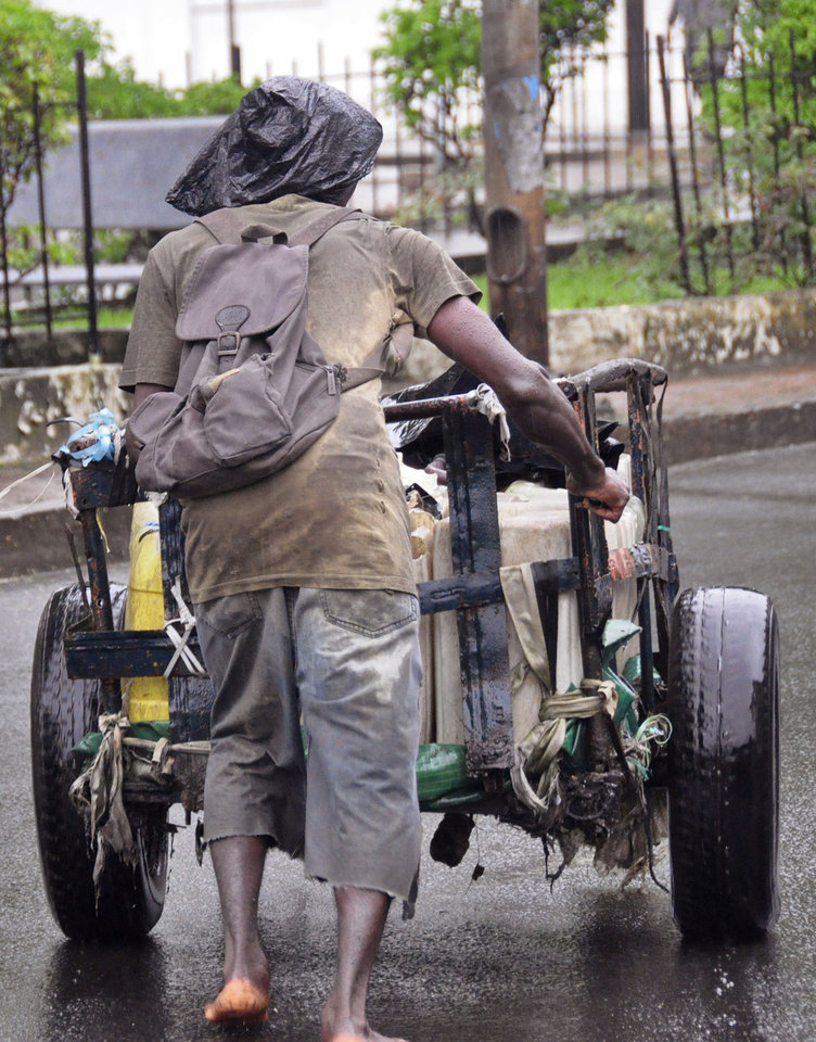 Photo - A man with a plastic bag on his head as protection against the rain, pushes his makeshift wheelbarrow filled with water containers as he sells water in Monrovia, Liberia, Thursday, Aug. 21, 2014. Calm returned Thursday to a slum in the Liberian capital that was sealed off in the government's attempt to halt the spread of Ebola, a day after clashes erupted between residents and security forces, but now the tens of thousands of residents are worried about getting food. (AP Photo/Abbas Dulleh)