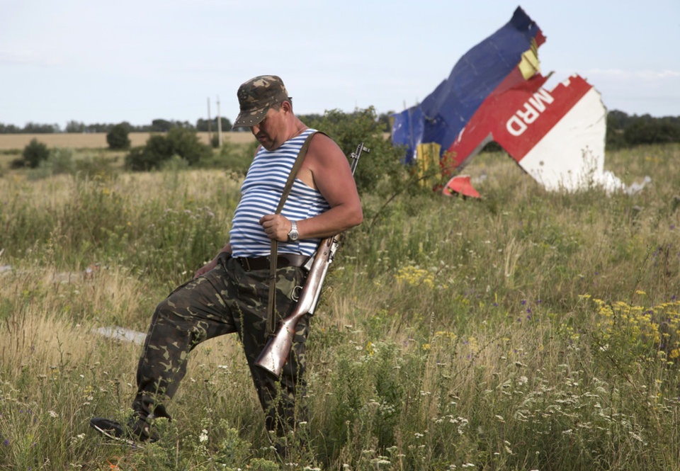 Photo - A pro-Russian fighter walks past a piece of the crashed Malaysia Airlines Flight 17 near the village of Hrabove, eastern Ukraine Monday, July 21, 2014. Four days after Flight 17 was shot out of the sky, international investigators still have had only limited access to the crash site, hindered by pro-Russia fighters who control the verdant territory in eastern Ukraine. Outrage over the delays and the possible tampering of evidence at the site was building worldwide, especially in the Netherlands, where most of the victims were from. (AP Photo/Dmitry Lovetsky)
