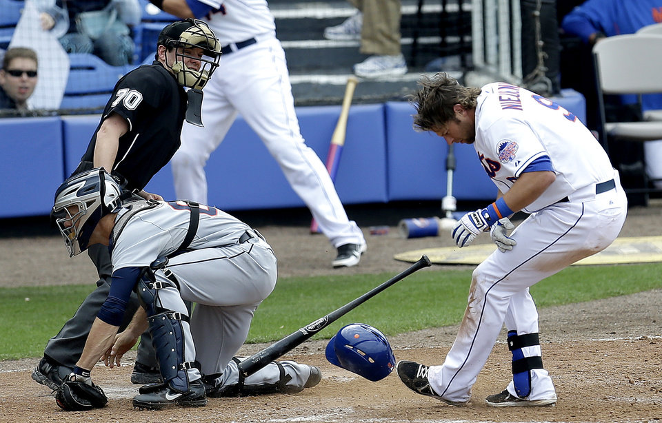 Photo - New York Mets' Kirk Nieuwenhuis (9) loses his helmet while being hit by a pitch by Detroit Tigers pitcher Duane Below during the sixth inning of an exhibition spring training baseball game, Friday, March 1, 2013, in Port St. Lucie, Fla. At left is Tigers catcher Brayan Pena and home plate umpire D.J. Reyburn.  (AP Photo/Julio Cortez)