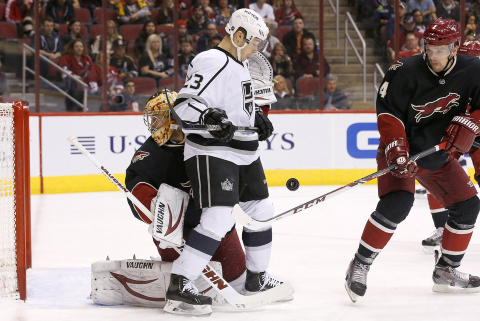 Photo - Phoenix Coyotes' Zbynek Michalek (4), of the Czech Republic, gets the stick on the puck in front of Los Angeles Kings' Dustin Brown (23) and Coyotes goalie Thomas Greiss, left, of Germany, during the first period of an NHL hockey game, Tuesday, Jan. 28, 2014, in Glendale, Ariz. (AP Photo/Ross D. Franklin)