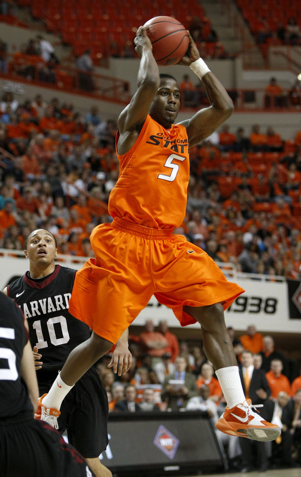 Photo - Oklahoma State's Reger Dowell (5) passes the ball in front of Harvard's Brandyn Curry (10) during a first-round NIT college basketball game between Oklahoma State University (OSU) and Harvard at Gallagher-Iba Arena in Stillwater, Okla., Tuesday, March 15, 2011. Photo by Bryan Terry, The Oklahoman