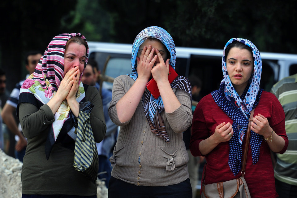 Photo - People attend a mine accident victim's burial in Soma, Turkey, Wednesday, May 14, 2014. Nearly 450 miners were rescued, the mining company said, but the fate of an unknown number of others remained unclear as bodies are still being brought to the surface and burials are underway after one of the world's deadliest mining disasters. (AP Photo/Emre Tazegul)