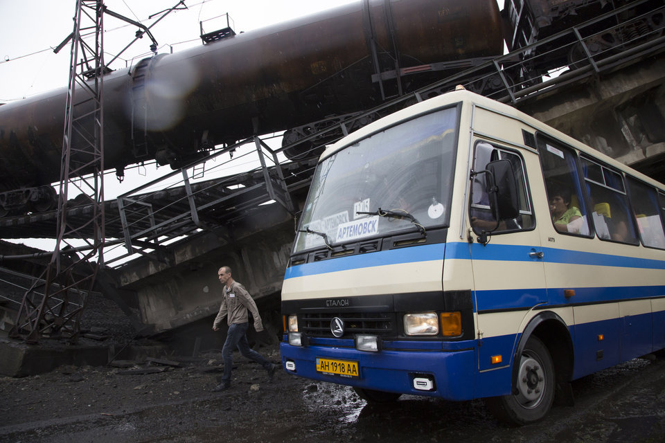 Photo - A man walks near a bus driven under a destroyed railroad bridge, near the village of Novobakhmutivka, 20 km North from the city of Donetsk, eastern Ukraine Monday, July 7, 2014. The bridge has been destroyed, blocking a key access route to the rebel-held city. (AP Photo/Dmitry Lovetsky)