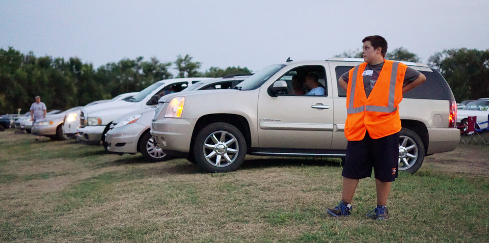 Photo - Sam Dick, 14, works as a parking volunteer to get the cars lined up at the Airline Drive-in movie theater in Ponca City Thursday, August 14, 2014. Photo by Doug Hoke, The Oklahoman