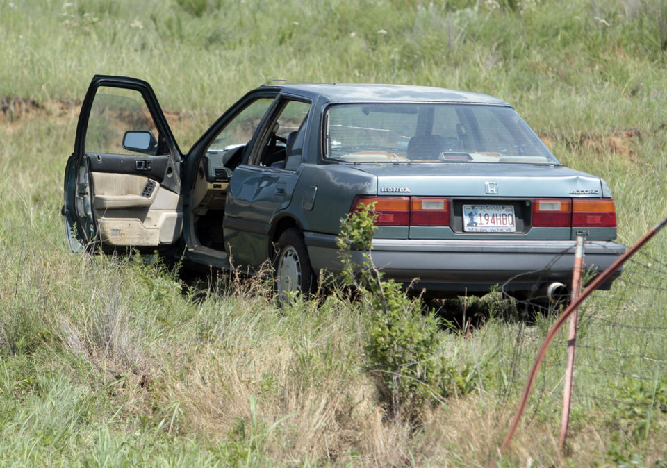 Photo - A damaged vehicle sits off the roadway at the scene where two pedestrians were killed on northbound Interstate 35 at the 102 marker on Saturday, June 9, 2012, in Purcell, Okla.   In a separate but related accident, a female passenger on a motorcycle was killed when the driver swerved to avoid backed up traffic at the 98 mile marker and struck the cable barrier.   Photo by Steve Sisney, The Oklahoman