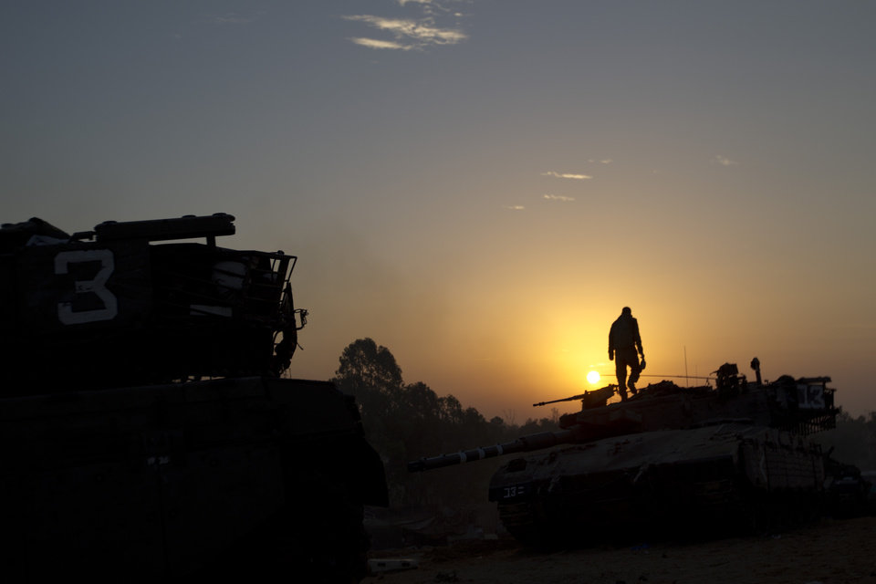 Photo -   An Israeli soldier stands on top of a military vehicle as the sun rises in a staging area near the Israel Gaza Border, southern Israel, Tuesday, Nov. 20, 2012. Israeli aircraft on Tuesday battered the headquarters of the bank Gaza's Hamas leaders set up to sidestep international sanctions on their rule, as fitful efforts to negotiate an end to a week-old convulsion of violence moved to the highest reaches of diplomacy. The strike on the Islamic National Bank was part of a widening Israeli assault against Gaza militants, meant to quell rocket fire that has abruptly struck deep into Israel's heartland. U.N. chief Ban Ki-moon will be in Egypt and Israel on Tuesday to try his hand at prodding the two sides to reach a deal. (AP Photo/Ariel Schalit)