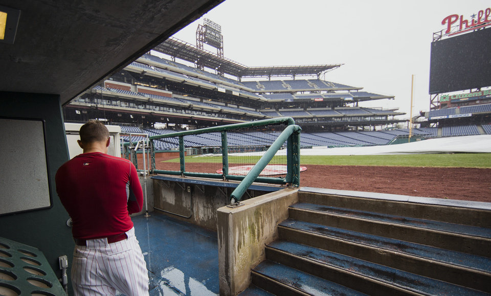 Photo - A Philadelphia Phillies' player stands in the dugout while a tarp covers the field as the exhibition baseball game between the Pittsburgh Pirates and the Philadelphia Phillies is canceled due to rain, Saturday, March 29, 2014, in Philadelphia. (AP Photo/Chris Szagola)