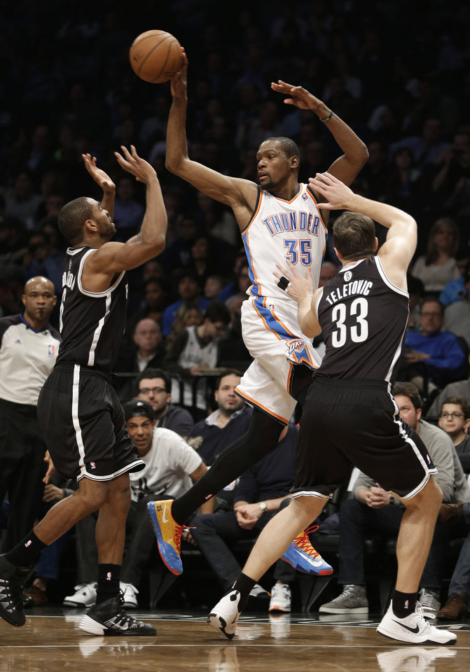 Photo - Oklahoma City Thunder's Kevin Durant, center, passes between Brooklyn Nets' Mirza Teletovic, right, and Alan Anderson during the first half of an NBA basketball game Friday, Jan. 31, 2014, in New York. (AP Photo/Seth Wenig)