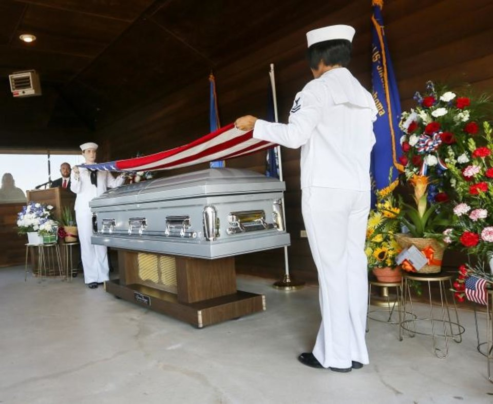 Photo -  Navy Petty Officer 2nd Class Elizabeth Franks, left, and Petty Officer 2nd Class Arielle Jackson fold a flag from Herman White's casket during the funeral service for the World War II veteran at Grace Hill Cemetery in Perry, Okla., Wednesday, Sept. 4, 2019. Hundreds of people attended Navy Seaman 2nd Class White's funeral after learning that he had no surviving family members to be there. [Nate Billings/The Oklahoman]