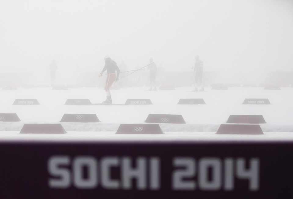 Photo - Athletes warm up in thick fog prior to the men's biathlon 15k mass start, at the 2014 Winter Olympics, Monday, Feb. 17, 2014, in Krasnaya Polyana, Russia. The men's 15-kilometer mass-start biathlon race at the Sochi Olympics has been delayed for an indefinite time due to fog, one day after the event had been called off for the same reason. (AP Photo/Gero Breloer)