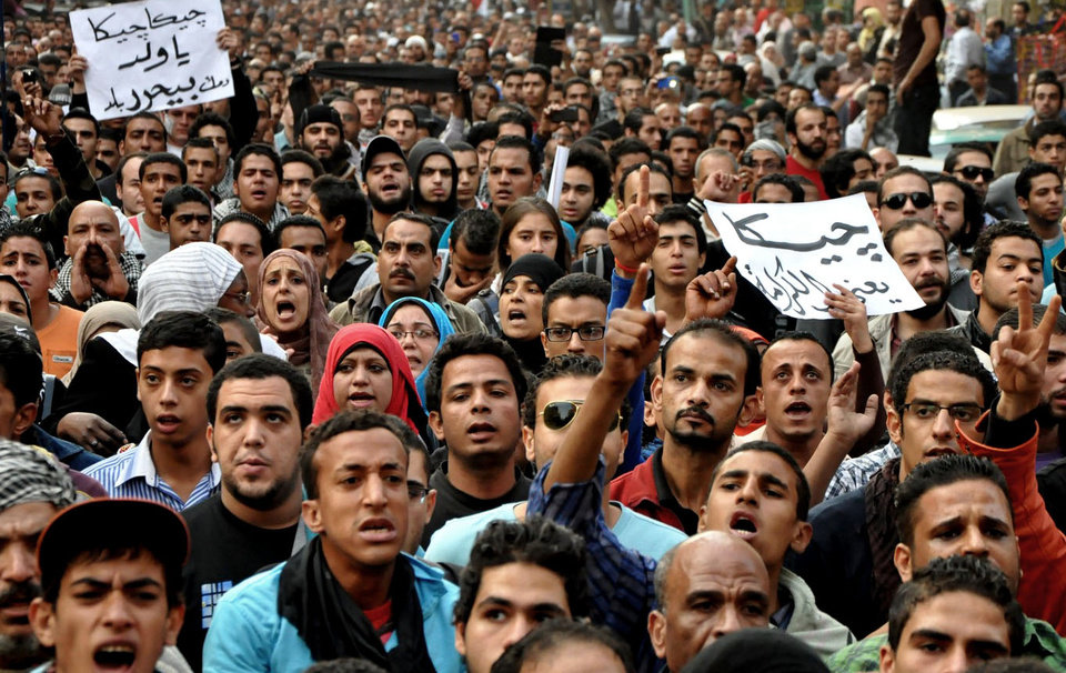 "Egyptians attend the funeral of Gaber Salah, also known as 'Jika,' who was who was killed in clashes with security forces during his funeral procession in Cairo, Egypt, Monday, Nov. 26, 2012. Thousands of Egyptians on Monday gathered into Cairo's Tahrir Square to attend the funeral of Salah, who was severely injured during clashes with security forces last week and died Sunday night. The poster at right in Arabic reads, ""Jika means dignity,"" and the poster, left, reads, ""Jika Jika, your blood will free our country."" (AP Photo/Hussein Tallal)"