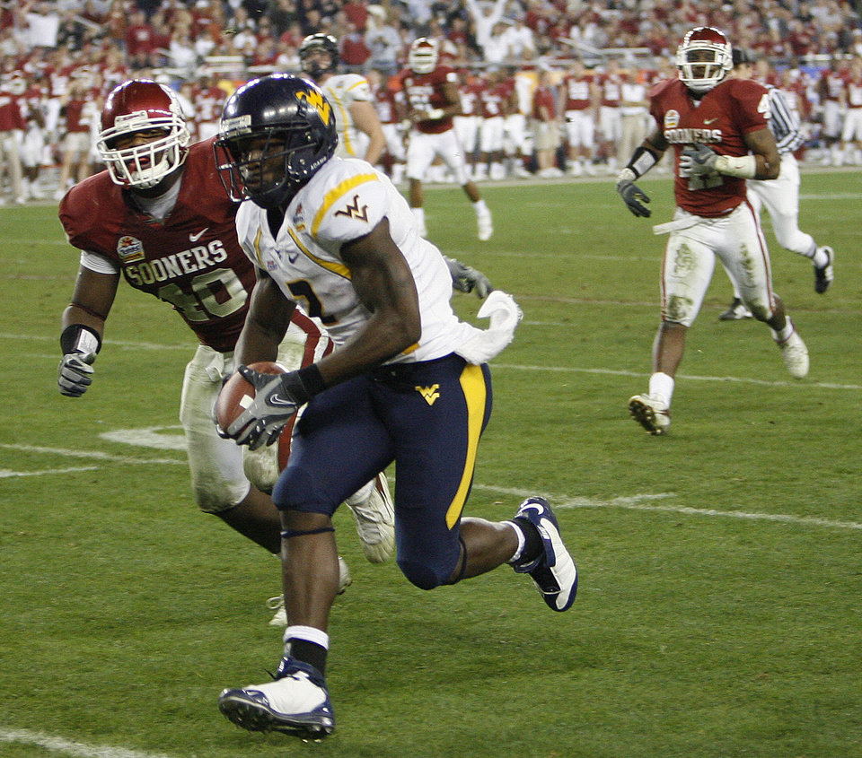 Photo - West Virginia's Darius Reynaud (2) makes his way past Oklahoma's Curtis Lofton (40) for a touchdown during the second half of the Fiesta Bowl college football game between the University of Oklahoma Sooners (OU) and the West Virginia University Mountaineers (WVU) at The University of Phoenix Stadium on Wednesday, Jan. 2, 2008, in Glendale, Ariz. 