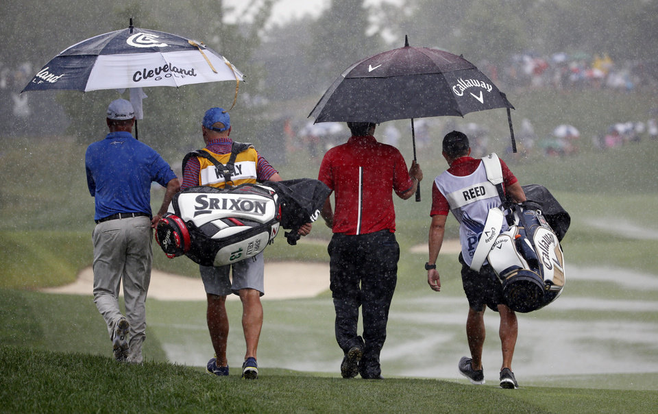 Photo - Jerry Kelly, left and Patrick Reed left the course during a rain delay in the final round of the PGA Championship golf tournament at Valhalla Golf Club on Sunday, Aug. 10, 2014, in Louisville, Ky. (AP Photo/Mike Groll)