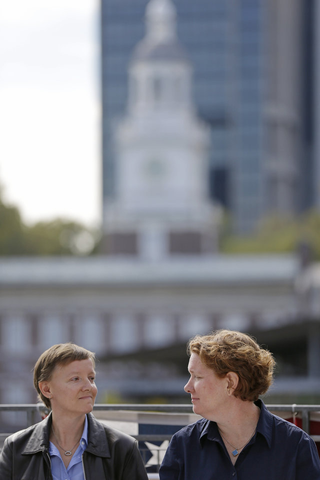 Photo - Plaintiffs Isabelle Barker, left, and her spouse Cara Palladino look at each other during a news conference, Thursday, Sept. 26, 2013, near Independence Hall in Philadelphia. Cara Palladino and Isabelle Barker, who were legally married in Massachusetts and moved to Pennsylvania, filed a federal lawsuit Thursday aiming to overturn the 1996 amendment to a state law stating same-sex marriages, including those recorded elsewhere, are not legal within the state.(AP Photo/Matt Rourke)