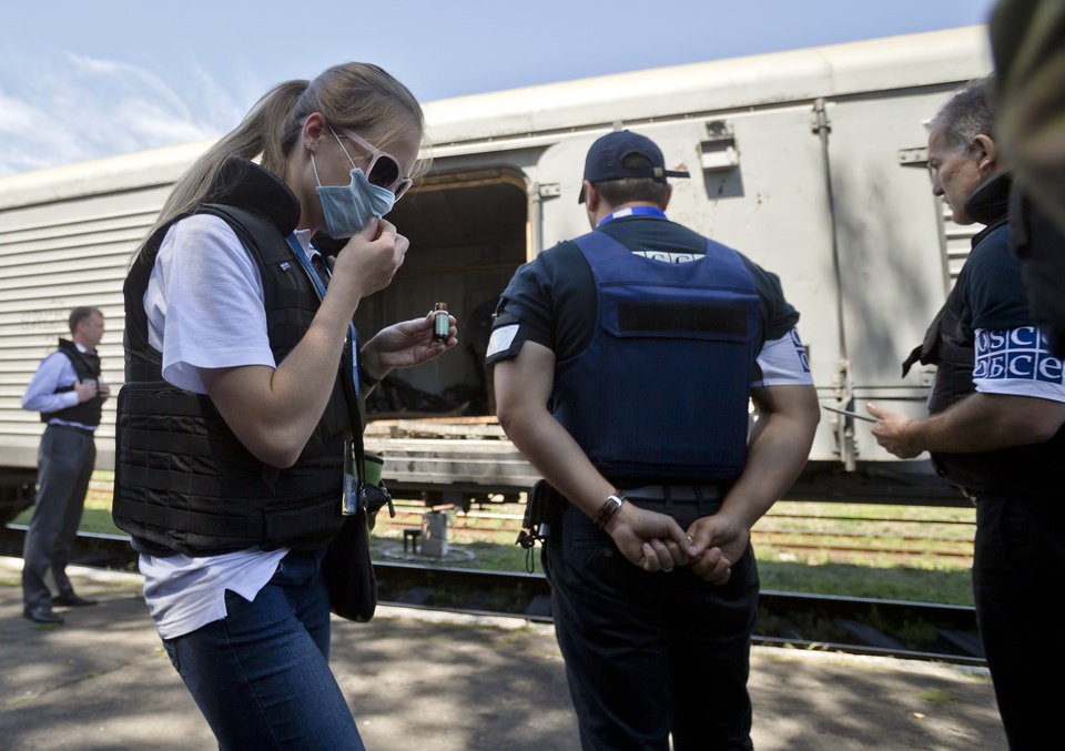 Photo - A members of the OSCE mission to Ukraine uses a chemical to combat the smell of decomposing bodies while inspecting along with Holland's National Forensic Investigations Team a refrigerated train loaded with the bodies of passengers in Torez, eastern Ukraine, 15 kilometers (9 miles) from  the crash site of Malaysia Airlines Flight 17, Monday, July 21, 2014. Another 21 bodies have been found in the sprawling fields of east Ukraine where Malaysia Airlines Flight 17 was downed last week, killing all 298 people aboard. International indignation over the incident has grown as investigators still only have limited access to the crash site and it remains unclear when and where the victims' bodies will be transported. (AP Photo/Vadim Ghirda)
