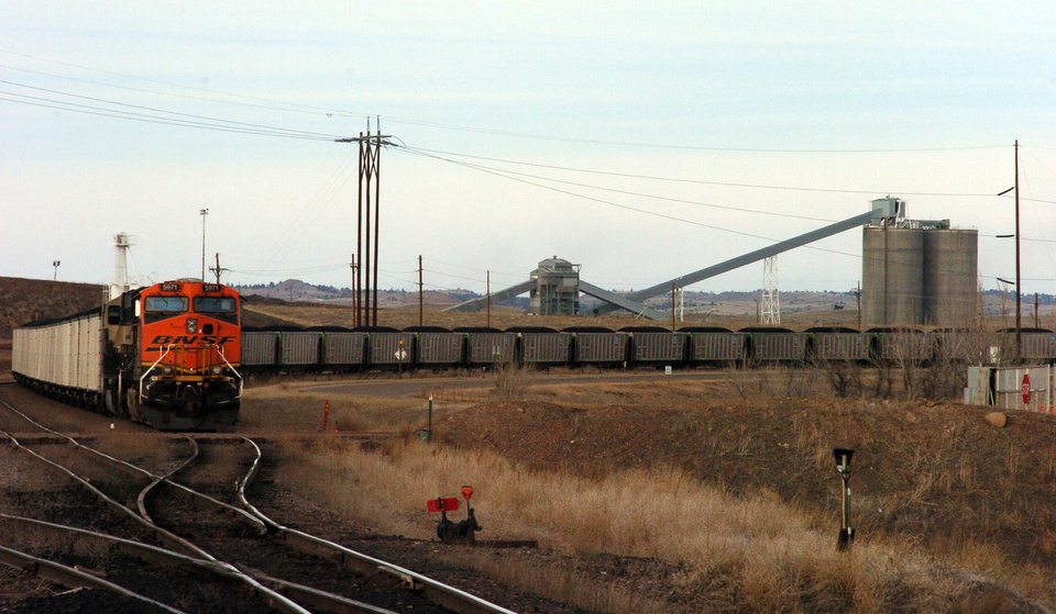 Photo - In this Jan. 16, 2013 photo, a coal train idles in front of the Decker Coal Mine near the Wyoming border in  Decker, Mont. The mine once produced 10 million tons of coal a year