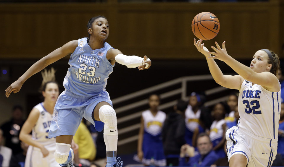 Photo - North Carolina's Diamond DeShields (23) and Duke's Tricia Liston (32) chase the ball during the second half of an NCAA college basketball game in Durham, N.C., Monday, Feb. 10, 2014. North Carolina won 89-78. (AP Photo/Gerry Broome)