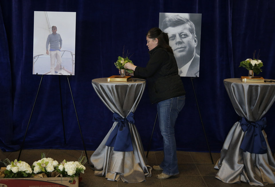 Photo - A woman arranges flowers at the sign in tables in the John F. Kennedy Presidential Library and Museum before visitors arrive Friday Nov. 22, 2013 in Boston. Kennedy, the 35th President of the United States, was assassinated in Dallas 50 years ago today. (AP Photo/Stephan Savoia)