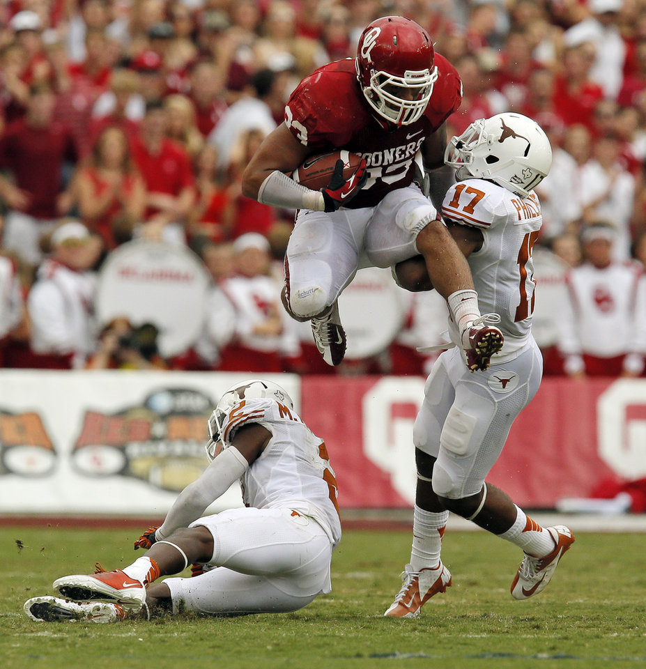 Photo - OU's Trey Millard (33) leaps over UT's Mykkele Thompson (2) and pushes away Adrian Phillips (17) in the second quarter during the Red River Rivalry college football game between the University of Oklahoma (OU) and the University of Texas (UT) at the Cotton Bowl in Dallas, Saturday, Oct. 13, 2012. OU won, 63-21. Photo by Nate Billings, The Oklahoman