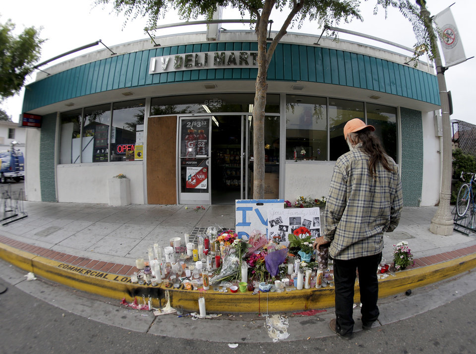 Photo - A passerby pays his respects at a makeshift memorial in front of the IV Deli Mart, Sunday, May 25, 2014, the scene of a drive-by shooting Friday in the Isla Vista area near Goleta, Calif. Calif. Sheriff's officials said Elliot Rodger, 22, went on a rampage near the University of California, Santa Barbara, stabbing three people to death at his apartment before shooting and killing three more in a crime spree through a nearby neighborhood. (AP Photo/Chris Carlson)