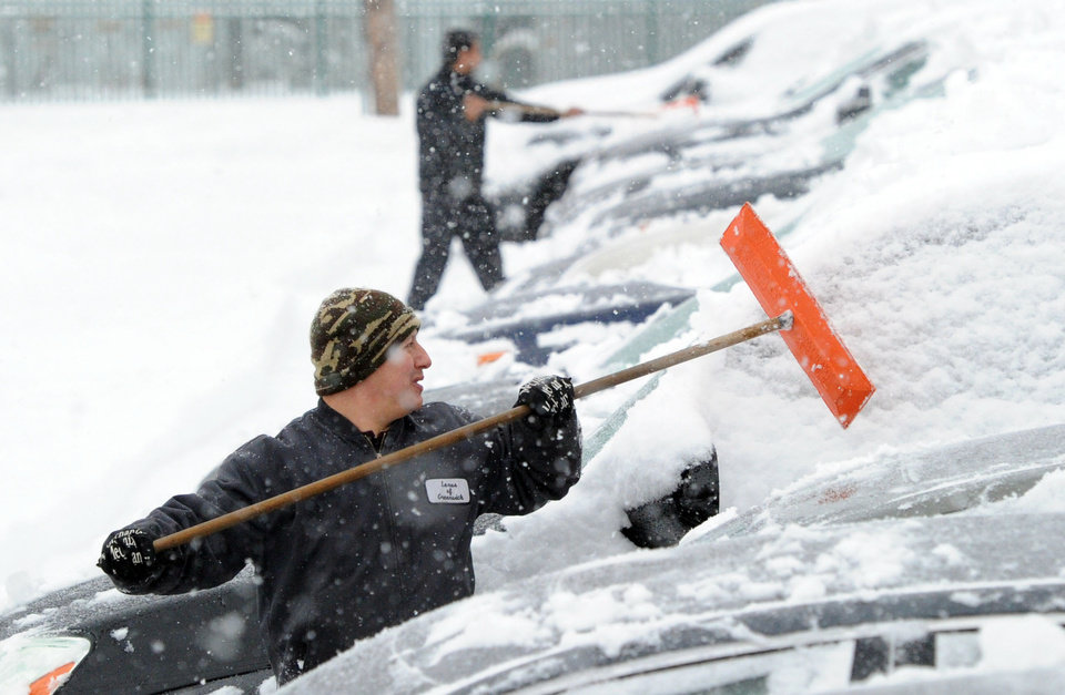 Photo - Julio Sanchez cleans snow from automobiles at a car dealership on Railroad Avenue during the snowstorm that hit Greenwich, Conn., Thursday, Feb. 13, 2014. The National Weather Service is forecasting a total possible accumulation of 10 inches of snow by the time the storm ends Friday morning. (AP Photo/The Greenwich Time, Bob Luckey)  MANDATORY CREDIT: GREENWICH TIME/BOB LUCKEY