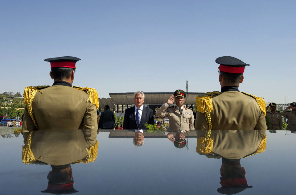 Photo - FILE - In this Wednesday, April 24, 2013, file photo, U.S. Secretary of Defense Chuck Hagel, second left, stands with an Egyptian army official before laying a wreath at the tomb of late President Anwar al-Sadat in Cairo. U.S. officials said Wednesday, Oct. 9, 2013, that the Obama administration is poised to slash hundreds of millions of dollars in military and economic assistance to Egypt. The U.S. has been considering such a move since the Egyptian military ousted the country's first democratically elected leader in June. (AP Photo/Jim Watson, Pool, File)