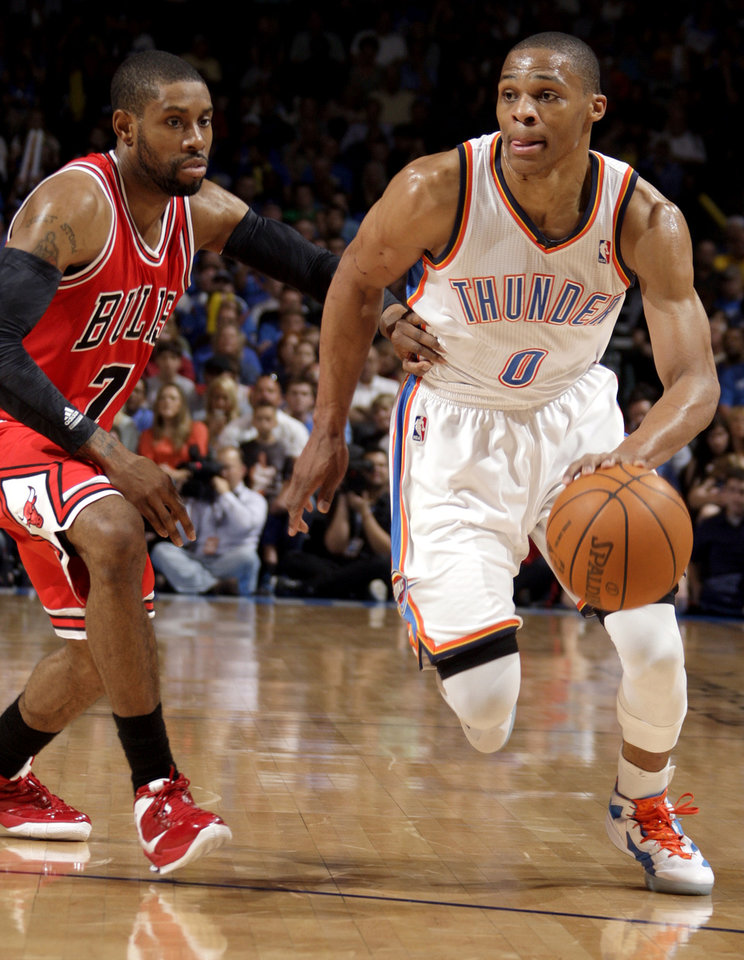 Oklahoma City's Russell Westbrook (0) dribbles past Chicago's C.J. Watson (7) during the NBA basketball game between the Chicago Bulls and the Oklahoma City Thunder at Chesapeake Energy Arena in Oklahoma City, Sunday, April 1, 2012. Photo by Sarah Phipps, The Oklahoman