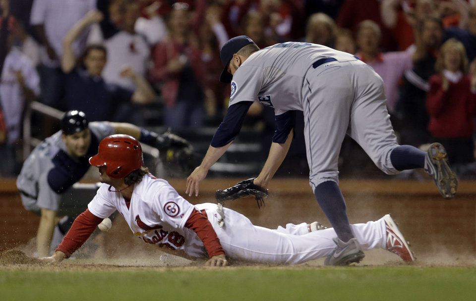 Photo - St. Louis Cardinals' Pete Kozma scores the game-winning run on a passed ball as Seattle Mariners relief pitcher Oliver Perez, right, covers home and catcher Mike Zunino, left, watches during the 10th inning of a baseball game Friday, Sept. 13, 2013, in St. Louis. The Cardinals won 2-1. (AP Photo/Jeff Roberson)