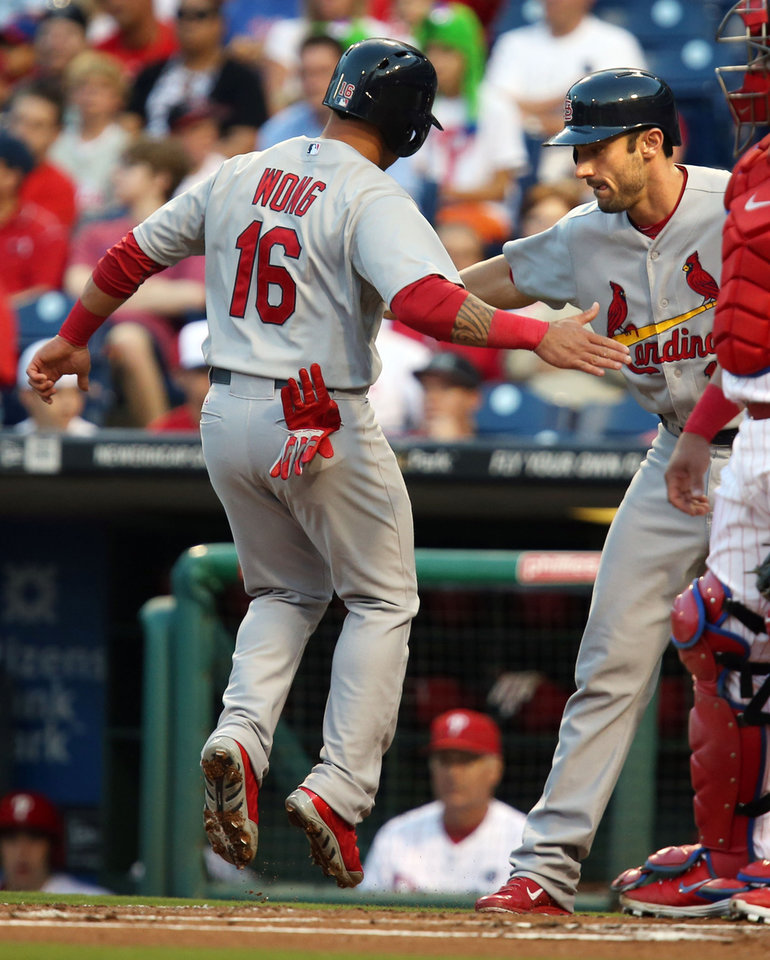 Photo - St Louis Cardinals Matt Carpenter, right, cheers on Kolten Wong after they both scored on a double by Matt Holliday in the first inning of a baseball game against the Philadelphia Phillies, Friday, Aug. 22, 2014, in Philadelphia. (AP Photo/Laurence Kesterson)