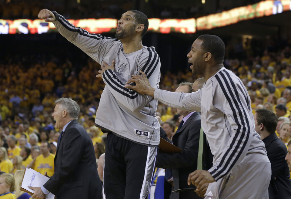 Photo - San Antonio Spurs power forward Tim Duncan, left, and shooting guard Tracy McGrady celebrate on the bench during the fourth quarter of Game 6 of a Western Conference semifinal NBA basketball playoff series against the Golden State Warriors in Oakland, Calif., Thursday, May 16, 2013. (AP Photo/Marcio Jose Sanchez)