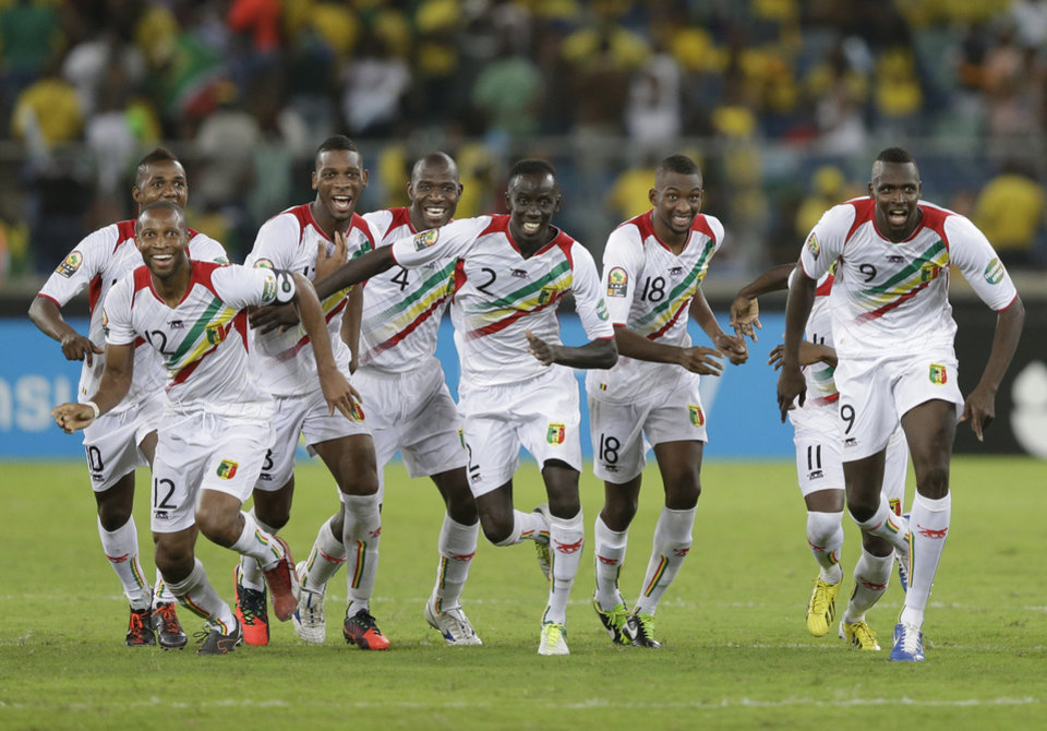 Photo - Mali players, including captain Seydou Keita, front left, react as they defeat host nation South Africa on penalties in their African Cup of Nations quarterfinal soccer match, at Moses Mabhida Stadium in Durban, South Africa, Saturday, Feb. 2, 2013. (AP Photo/Rebecca Blackwell)