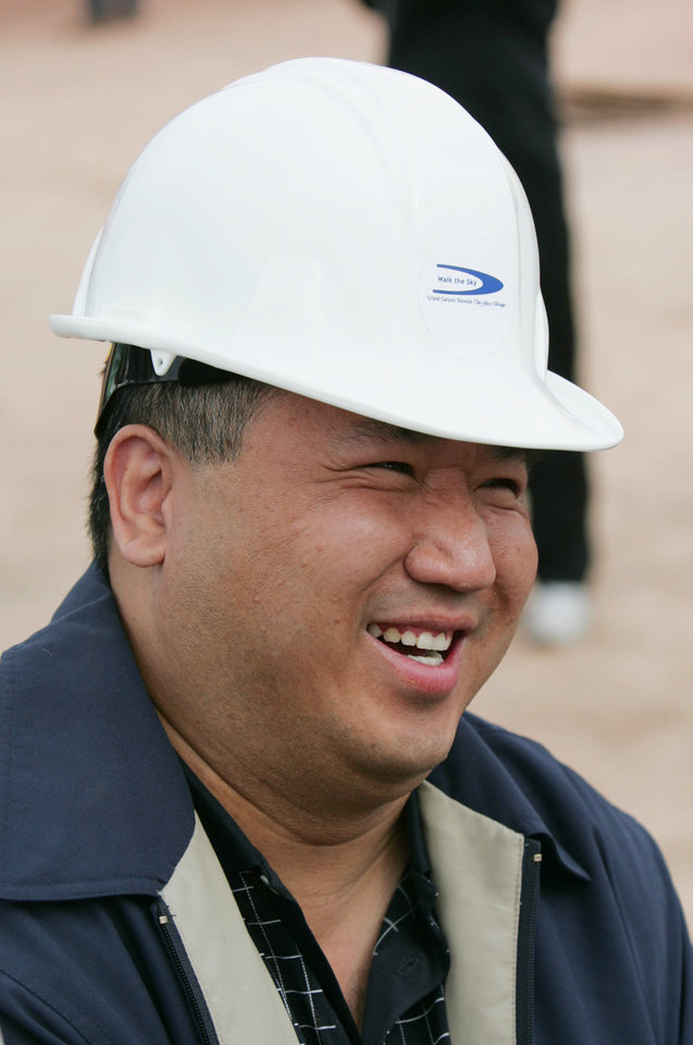 Photo - FILE- In this file photo taken March 7, 2007, David Jin, an investor for the Skywalk project, is all smiles at the rollout for the Skywalk on the Hualapai Indian Reservation in Grand Canyon West, Ariz. A federal court has upheld a $28 million judgment against a business arm of the northern Arizona tribe that owns the Grand Canyon Skywalk. The American Arbitration Association had awarded Las Vegas businessman David Jin the money in August. His attorneys went to federal court to enforce it. Jin invested $30 million to build the Skywalk, a glass bridge that gives visitors a view of the Colorado River from the Hualapai reservation. (AP Photo/Ross D. Franklin, File)
