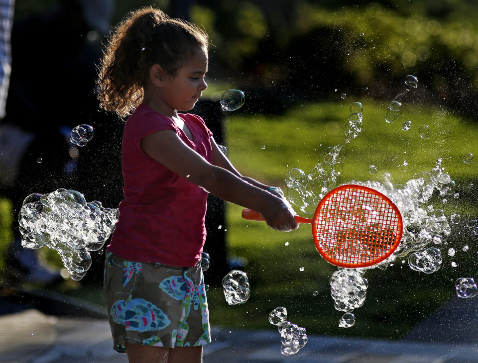 Taylor Long, 5, of Oklahoma City uses a wand to make bubbles during an event called Bubbles! at the pavilion at the Myriad Gardens in Oklahoma City, Saturday, August 10, 2013. The event, which will take place again on Sat., August 17, from 6:30-8:30,  was free to Myriad Gardens members and cost $2 per nonmember child to play with various bubble makers, paint with bubbles, and more. Photo by Bryan Terry, The Oklahoman