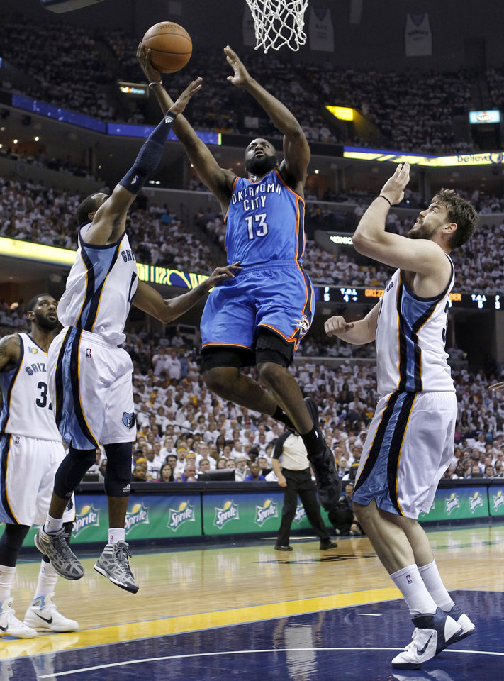 Oklahoma City Thunder guard James Harden (13) drives between Memphis Grizzlies defenders Mike Conley, left, and Marc Gasol, of Spain, right, during the first half of Game 4 of a second-round NBA basketball playoff series on Monday, May 9, 2011, in Memphis, Tenn. (AP Photo/Lance Murphey)